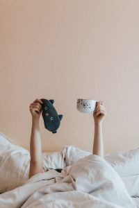 persona en la cama con antifaz y taza de te