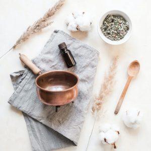 aceite esencial con flor de lavanda y cazo de cobre sobre tela de lino