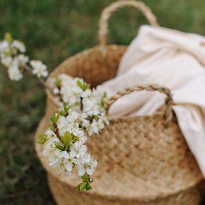 cesto vegetal con flor de espino blanco y chal rosa