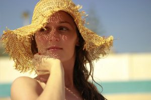 mujer morena con sombrero amarillo tomando el sol