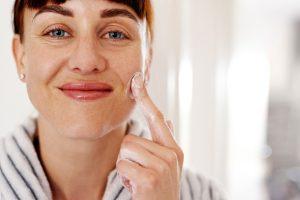 mujer aplicando crema hidratante facial