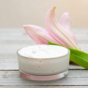 crema hidratante con flor rosada al lado sobre mesa de madera clara